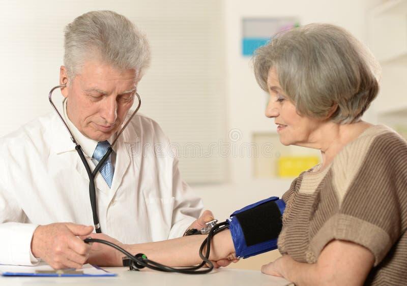 Elderly doctor measuring royalty free stock photo