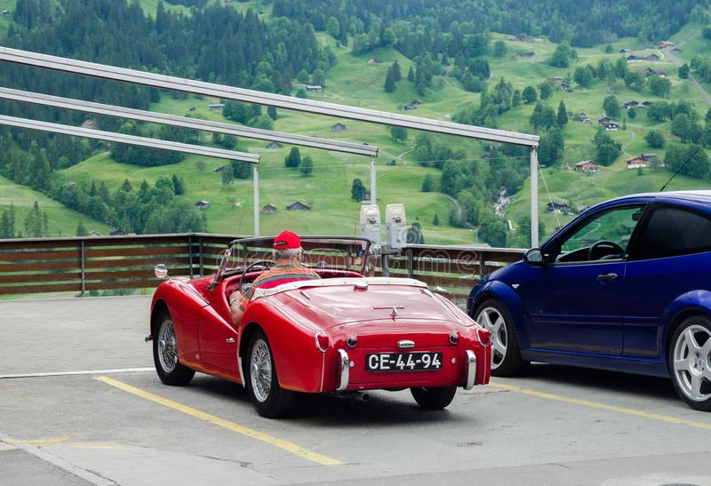 Elderly driver in Triumph TR3 red oldtimer car. GRINDELWALD, SWITZERLAND - JUNE 14, 2013: Elderly driver in Triumph TR3 red oldtimer car stock photography