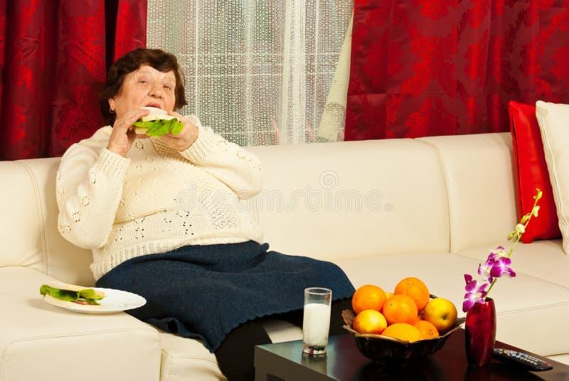 Elderly eating sandwich home royalty free stock image