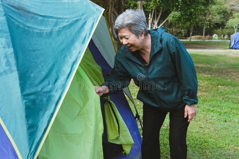 elderly elder senior woman opening going into tourist camping tent. senior leisure outdoors lifestyle royalty free stock photography