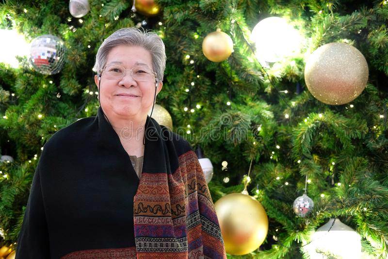 Elderly elder woman female senior smiling at christmas tree. xmas new year holiday. Festival stock image