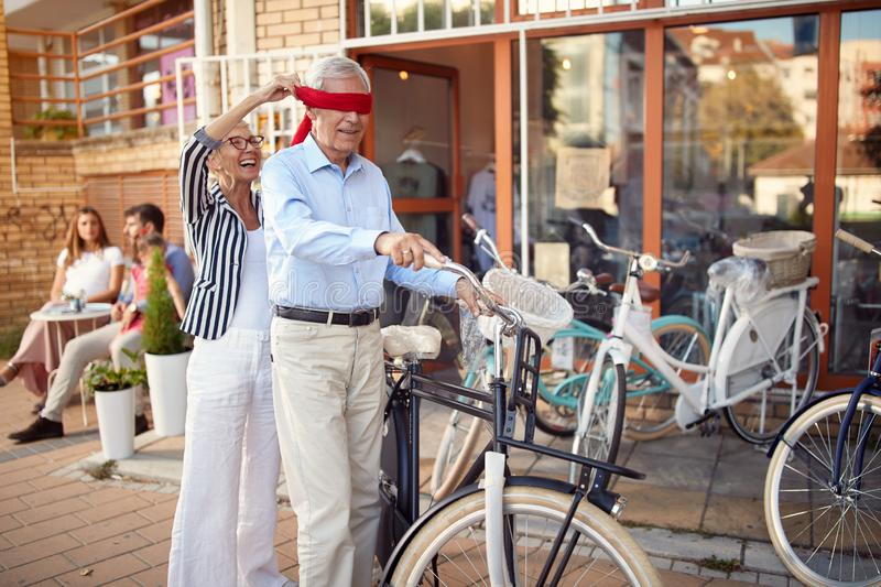 Elderly family in shopping buying new bicycle for surprise. Happy elderly family in shopping buying new bicycle for surprise royalty free stock image