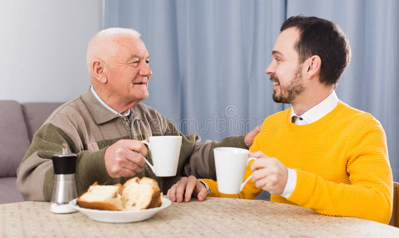 Elderly father and son breakfast. Smiling elderly father and son having breakfast and warmly talk at table at home stock image