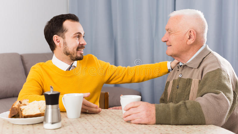 Elderly father and son breakfast. Elderly father and son together having breakfast at table and friendly communicate royalty free stock image