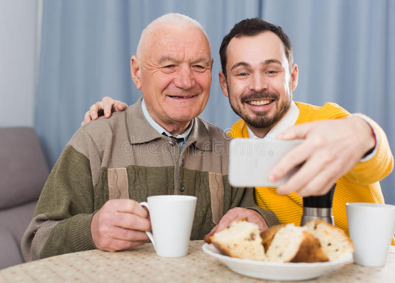 Elderly father and son doing selfie stock image