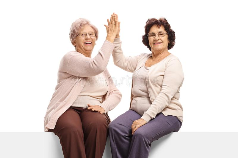 Elderly female frends sitting on a panel high-fiving each other and looking at the camera. Isolated on white background stock images