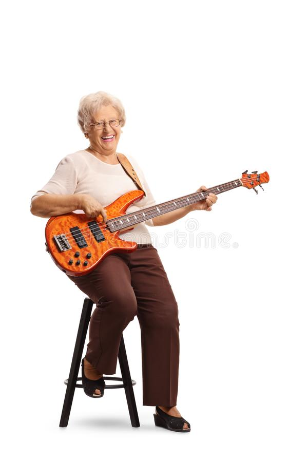Elderly female guitarist with an electric bass guitar sitting on a chair. Full length portrait of an elderly female guitarist with an electric bass guitar royalty free stock photography