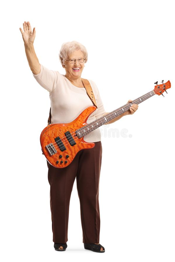 Elderly female guitarist with an electric bass guitar waving at the camera. Full length portrait of an elderly female guitarist with an electric bass guitar stock photo