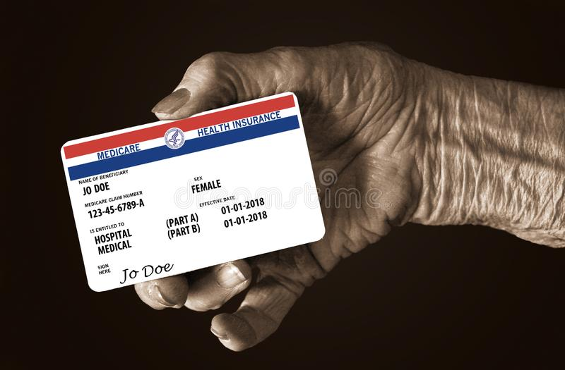 An elderly female hand holds a mock United State government Medicare Health Insurance card. It is a generic card. This is a photo illustration royalty free stock photos