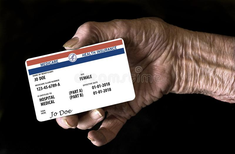 An elderly female hand holds a mock United State government Medicare Health Insurance card. It is a generic card. This is a photo illustration royalty free stock image