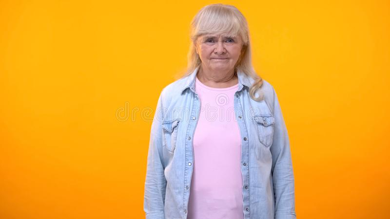 Elderly female with serious look isolated on orange template, retirement age. Stock photo royalty free stock photography