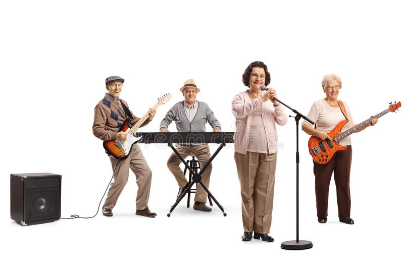 Elderly female singing and an elderly men and woman playing guitars and keyboard. Full length portrait of an elderly female singing and an elderly men and women stock photography