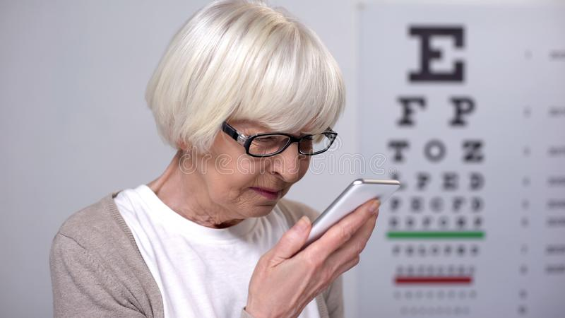 Elderly female trying to read on smartphone, small font, poor vision problem royalty free stock photo