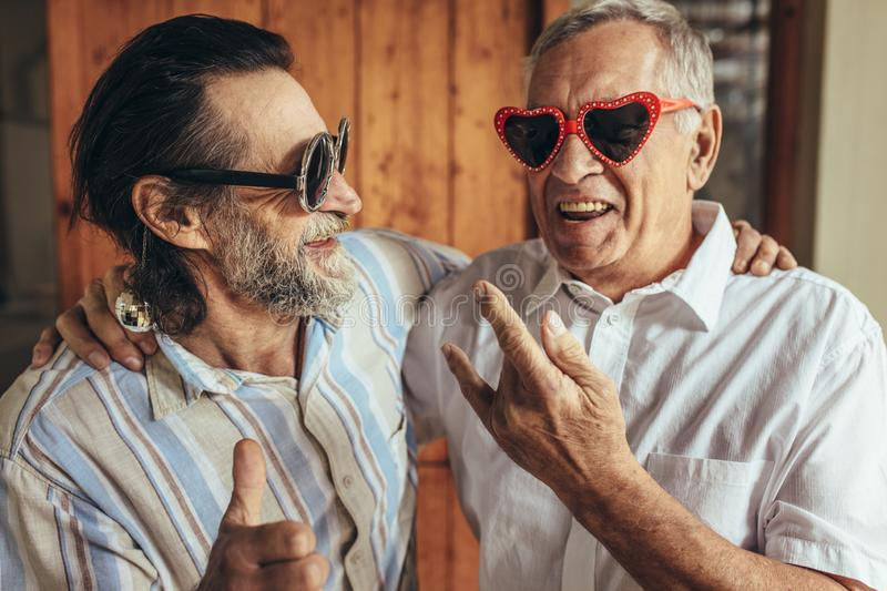 Elderly friends with crazy eyewear having fun. Happy old men wearing funny sunglasses making funky gestures. Elderly friends with crazy eyewear having fun royalty free stock images