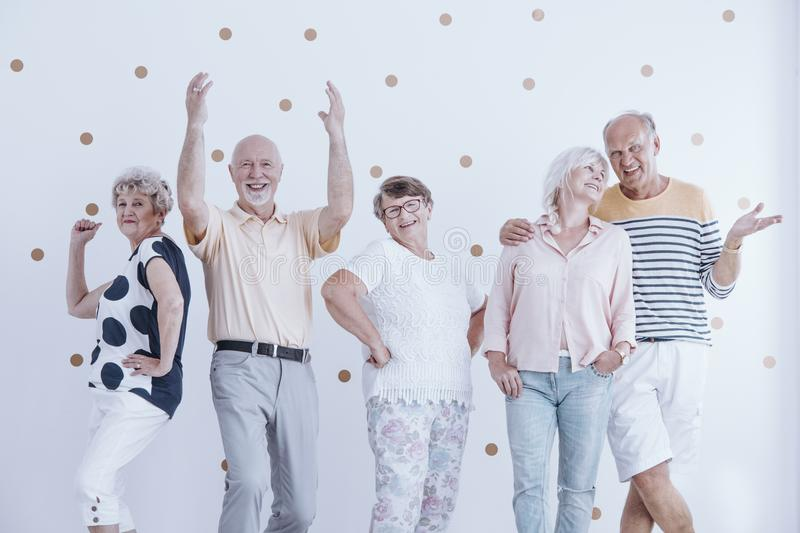 Elderly friends dancing and talking stock photography