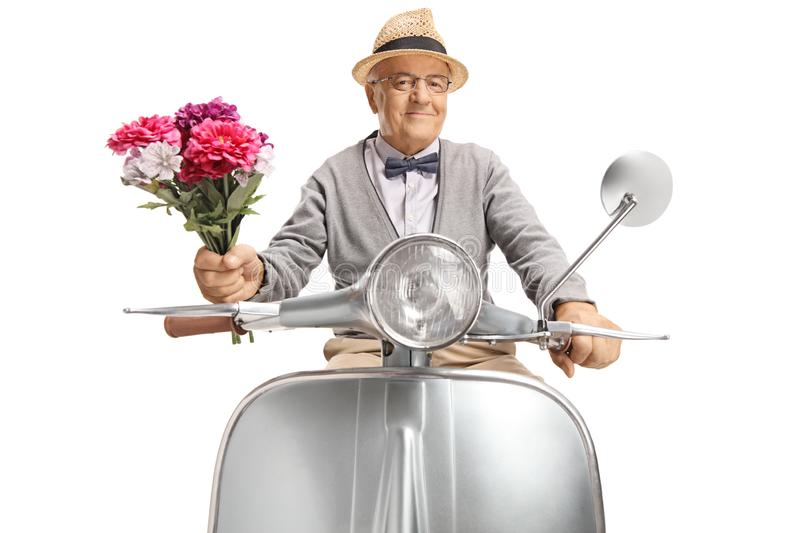Elderly gentleman on a motorbike holding a bunch of flowers stock images