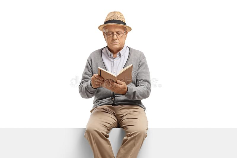 Elderly gentleman sitting on a panel reading a book stock photos
