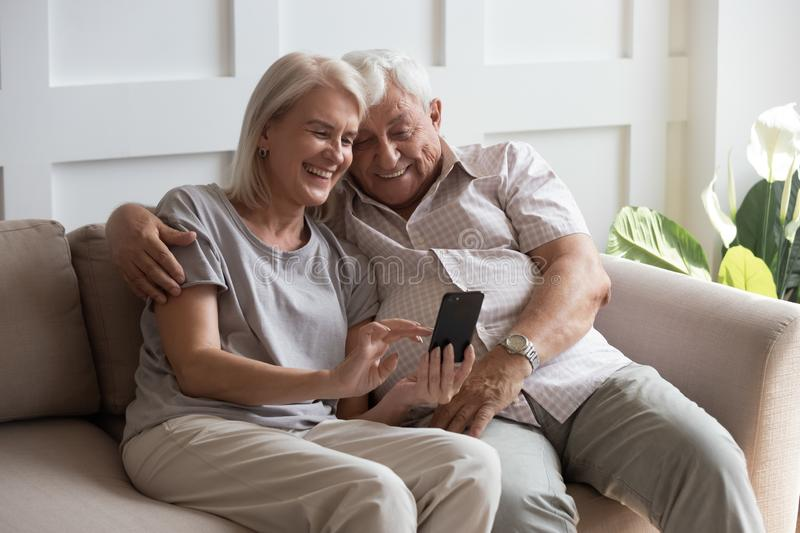 Elderly grandfather and grandmother spend time having fun using smartphone. Apps, middle-aged wife enjoy online entertainments, taking selfie with old husband stock images