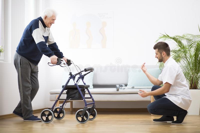 Elderly grandfather with walker trying to walk again and helpful male nurse supporting him stock photo