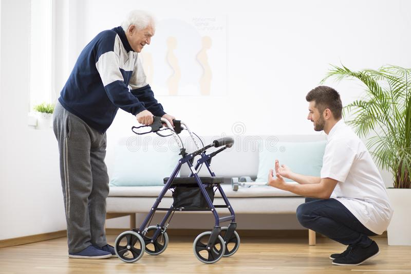 Elderly grandfather with walker trying to walk again and helpful male nurse supporting him royalty free stock images