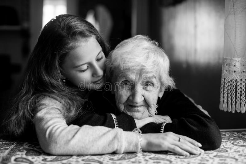 Elderly grandmother with her little girl granddaughter. Portrait black-and-white royalty free stock image