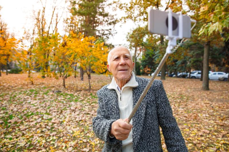 An elderly man in an autumn park and holds a monopod with a mobile phone. Outdoors on the street. stock photo