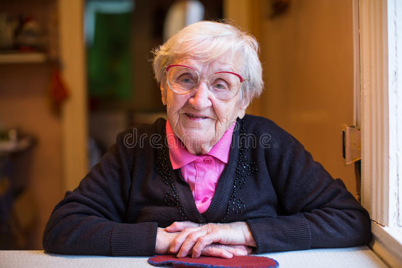 Elderly gray-haired woman in glasses stock photo