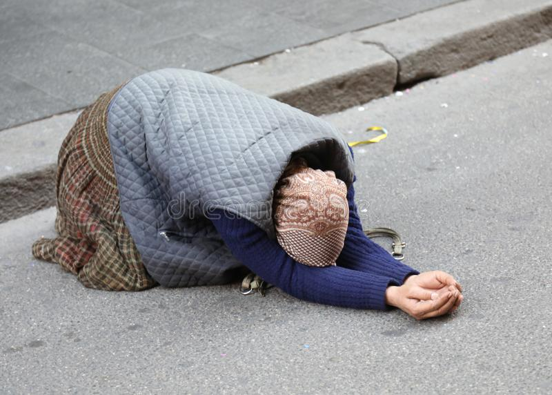 Elderly gypsy woman begging for passersby kneeling with her hand. Elderly gypsy woman begging for passersby kneeling on the ground with her hands clasped in stock photos