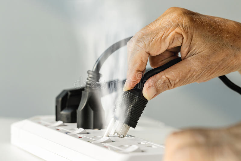 Elderly hand with electrical outlet spark stock image
