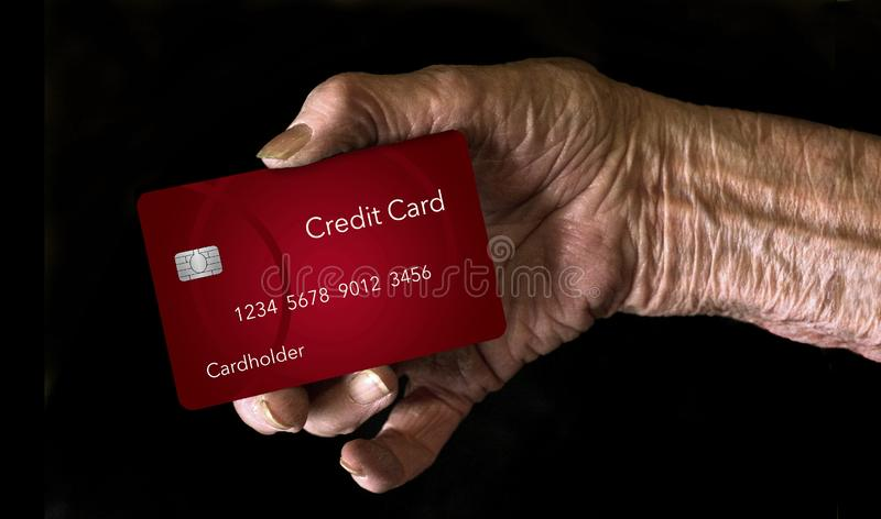 An elderly hand holds a credit card to illustrate the theme: Which credit card is best for older men and women. This is an illustration stock images