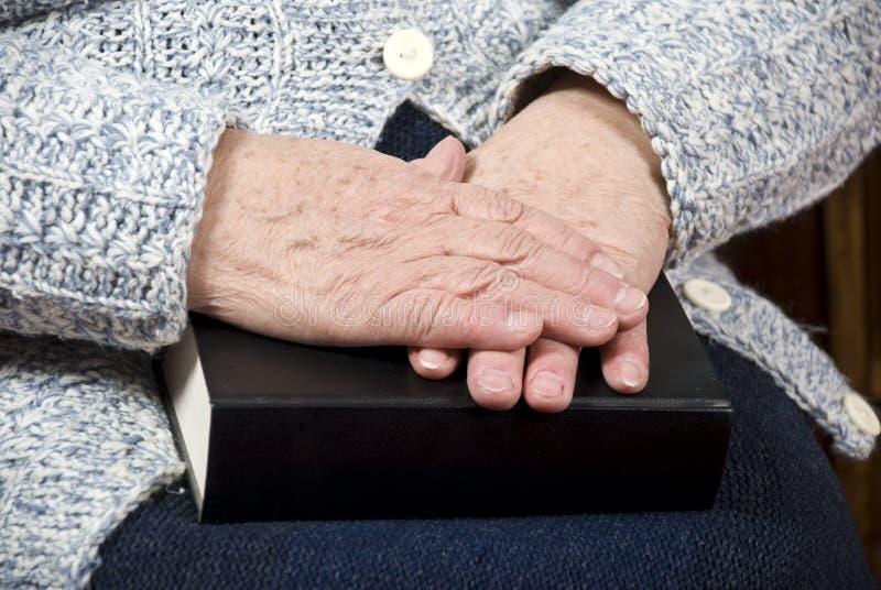 Elderly hands on bible stock photo