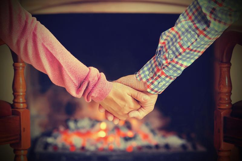 Woman and man hands on the background of the fireplace stock photography