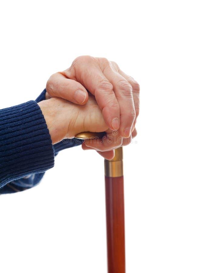 Elderly hands resting on stick stock image