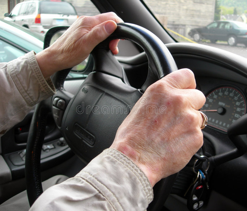 Elderly hands on steering wheel royalty free stock image