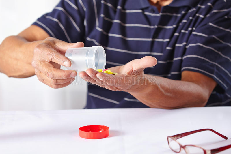 Elderly hands taking pills stock photo