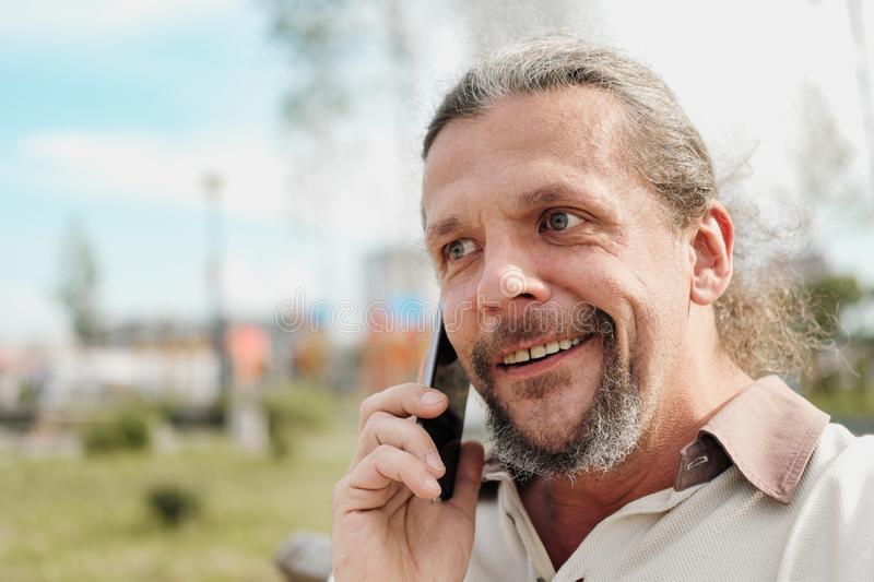An elderly handsome man with long hair in the tail emotionally speaks on a cell phone in a park on a bench. royalty free stock photography