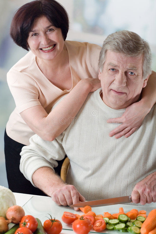 Elderly happy couple cooking at kitchen royalty free stock photos
