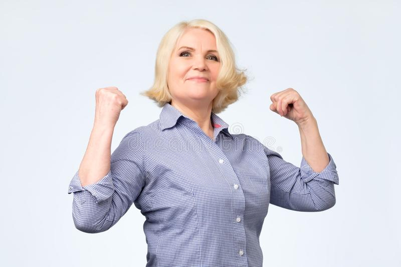 Elderly happy senior woman being proud of herself showing her muscles royalty free stock image