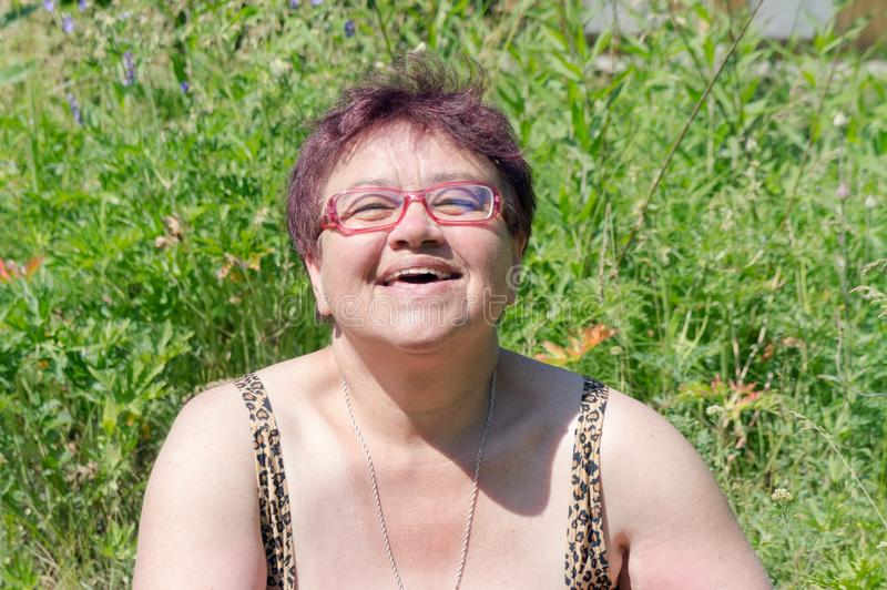 Elderly happy woman with glasses sunbathes in the grass under the bright summer sun stock photo