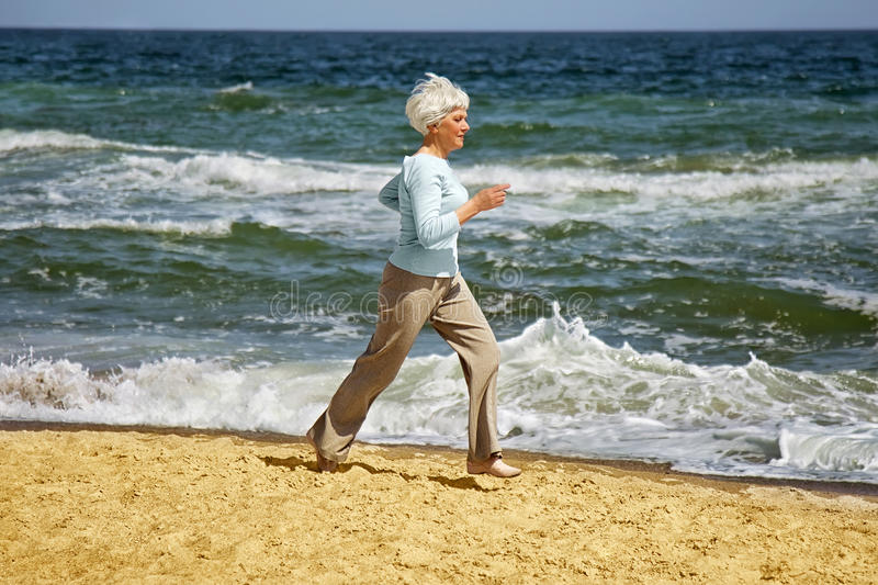 Elderly happy woman running on the beach along the coast near sea royalty free stock photography