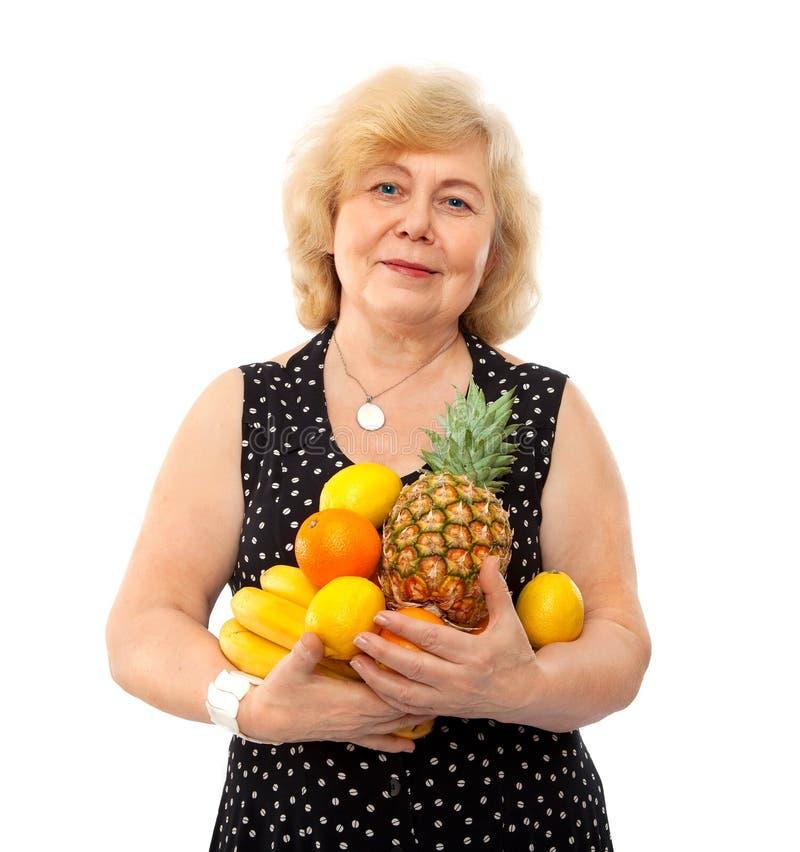Elderly happy woman treat fresh fruits stock photos