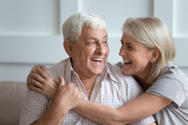 Elderly hoary couple embracing sitting on couch indoors. Cheerful 80s elderly husband and attractive blond 60s wife sitting on couch laughing embracing indoors stock photography