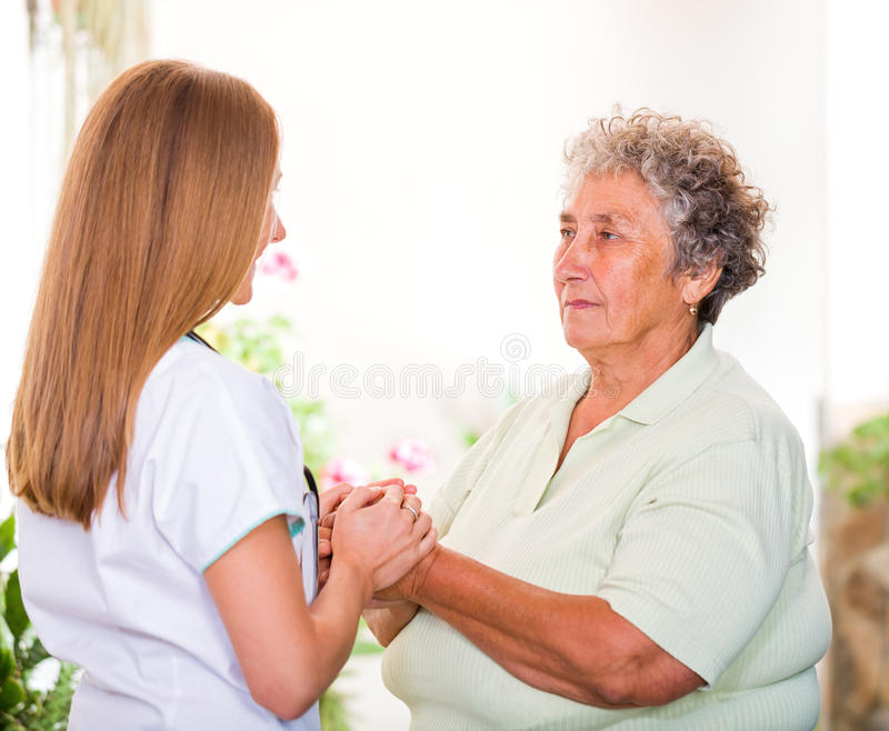 Elderly home care. Photo of elderly women with her caregiver royalty free stock photography