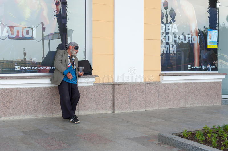 Elderly homeless man begging for some money near sport shop on a sea-front royalty free stock image