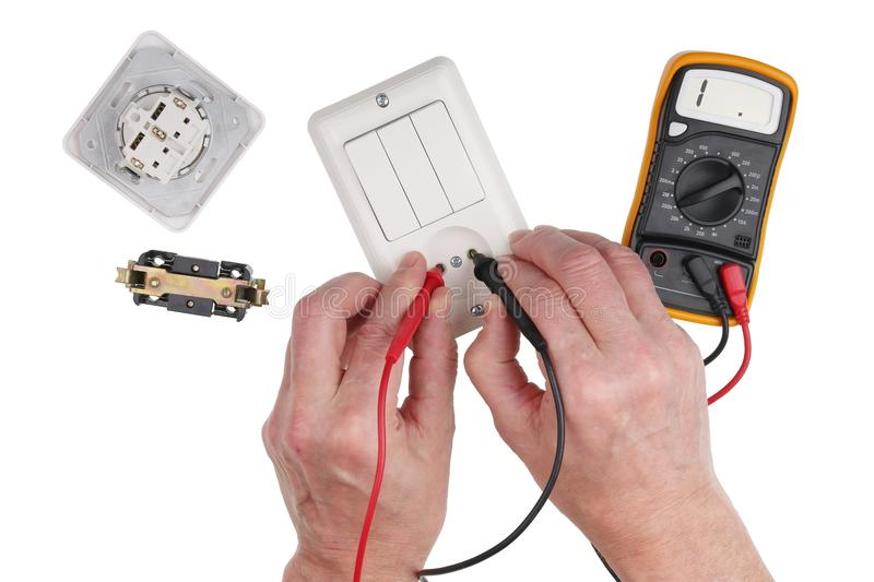 An elderly household electrician checks the isolation of the switch using a multimeter stock image