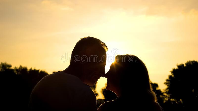Elderly husband and wife nuzzling, happy marriage, retired couple happiness stock image