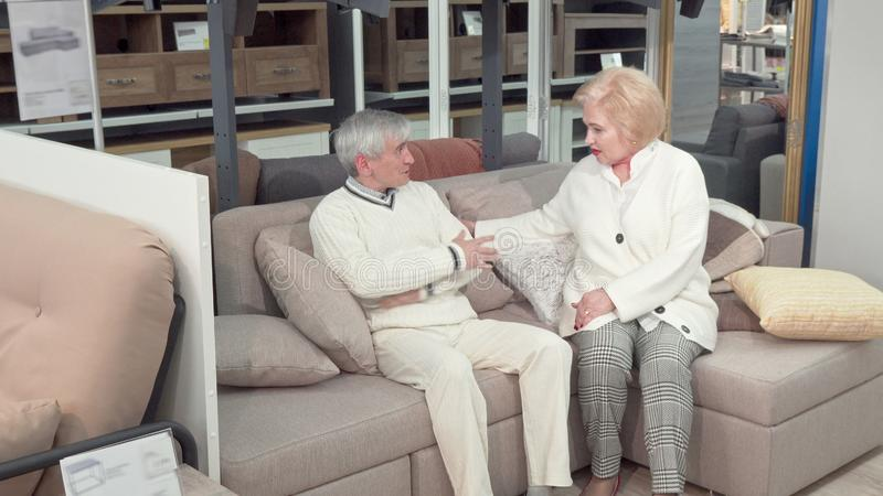 Elderly husband and wife trying new sofa, shopping for furniture. Lovely senior couple sitting on a couch at furnishings store. Elderly customers buying stock images