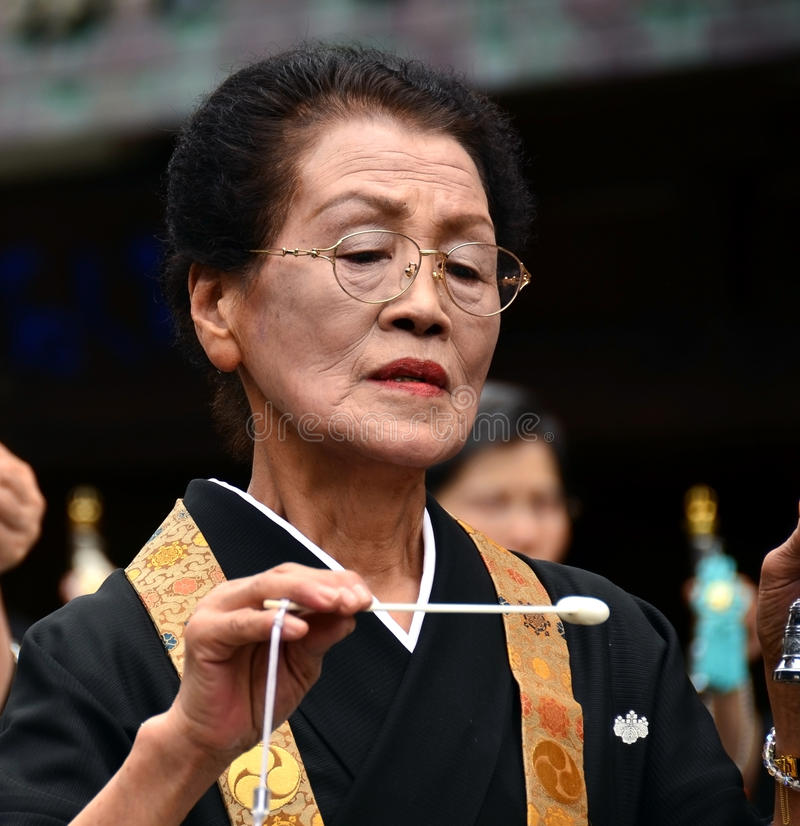 Elderly Japanese woman in formal Buddhist attire. Mount Koya, Japan - June 14, 2011: Woman in formal buddhist attire dancing and chanting during Aoba festival stock image