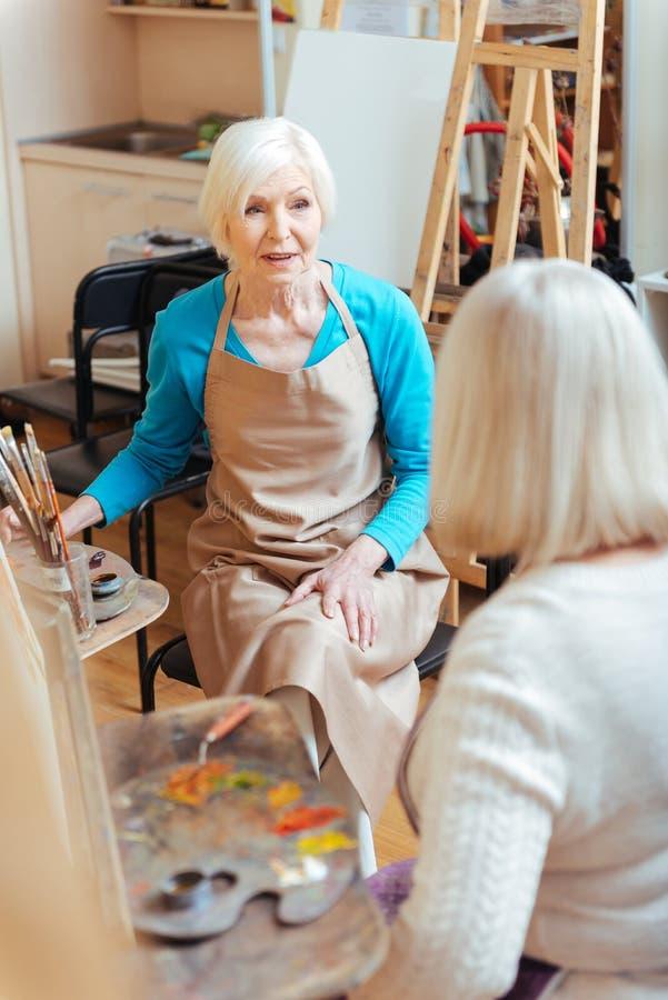 Elderly ladies talking in painting class stock photo