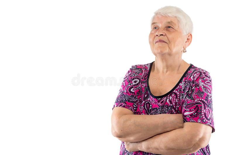 Elderly lady with arms crossed looking up. On white background stock photography